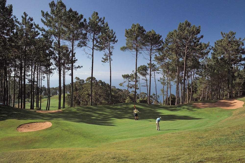 Golfeur sur le green entouré d'arbres sur le parcours de Palheiro